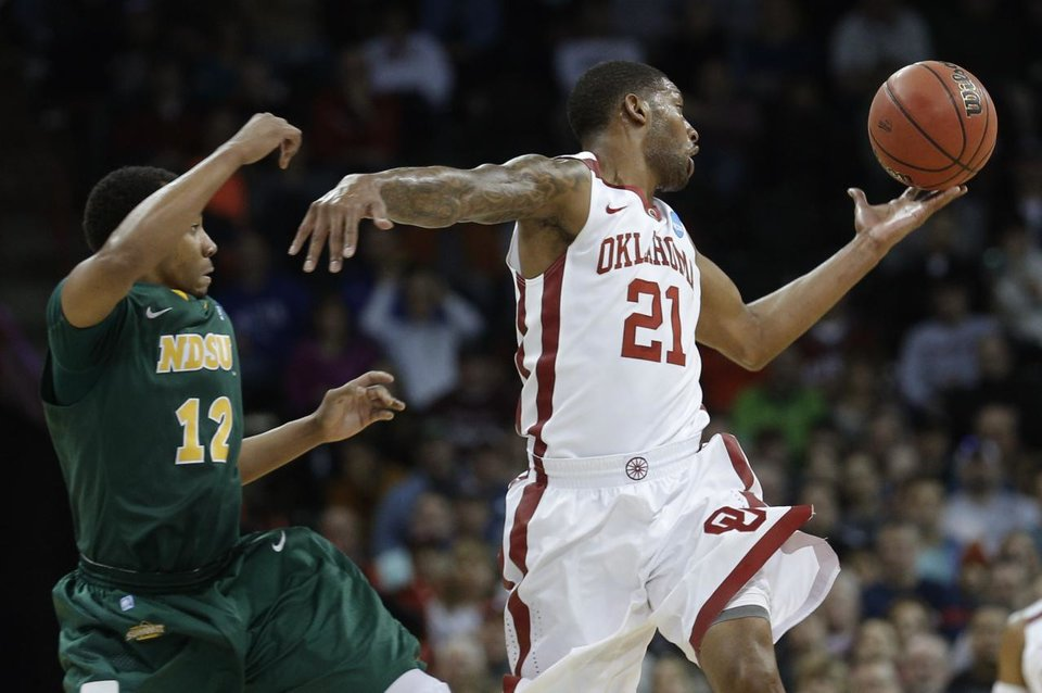 Photo - Oklahoma's Cameron Clark (21) grabs a loose ball from North Dakota State's Lawrence Alexander (12) during the NCAA men's basketball tournament game between the University of Oklahoma and North Dakota State at the Spokane Arena in Spokane, Wash., Thursday, March 20, 2014. Oklahoma home lost 80-75. Photo by Sarah Phipps, The Oklahoman
