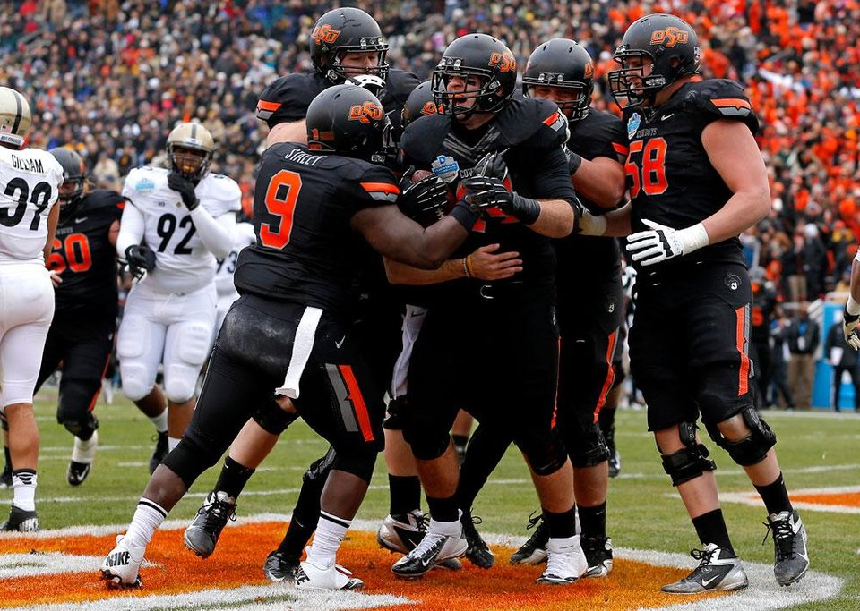 Oklahoma State's Jeremy Seaton (44) celebrates with Kye Staley (9), Daniel Koenig (58), and others after a touchdown during the Heart of Dallas Bowl football game between Oklahoma State University and Purdue University at the Cotton Bowl in Dallas, Tuesday, Jan. 1, 2013. Photo by Bryan Terry, The Oklahoman