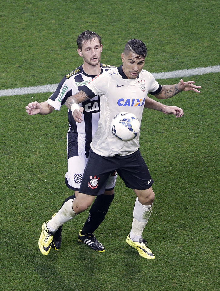 Photo - Corinthians's Paolo Guerrero, right, fights for a ball with Figueirense's Luan, during a Brazilian soccer league match at the Itaquerao, the still unfinished stadium, in Sao Paulo, Brazil, Sunday, May 18, 2014. Only 40,000 tickets were put on sale for Corinthians' match against Figueirense because some of the 20,000 temporary seats needed for the World Cup opener are still being installed. The stadium will host the World Cup opener match between Brazil and Croatia on June 12. (AP Photo/Andre Penner)