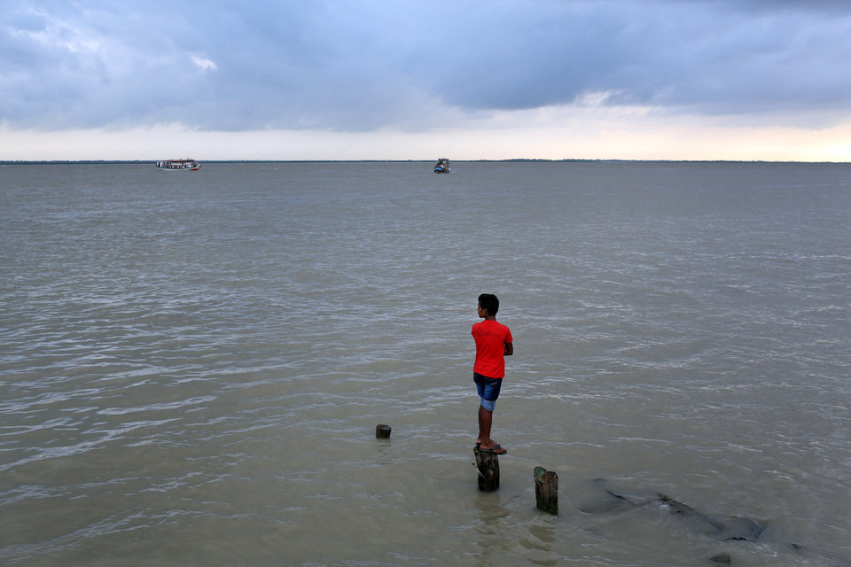 Photo - A Bangladeshi boy watches as rescuers search the River Padma after a passenger ferry capsized in Munshiganj district, Bangladesh, Monday, Aug. 4, 2014. A passenger ferry carrying hundreds of people capsized Monday in central Bangladesh, and at least 44 people either swam to safety or were rescued but the number of missing passengers is not yet known. (AP Photo/ A.M. Ahad)