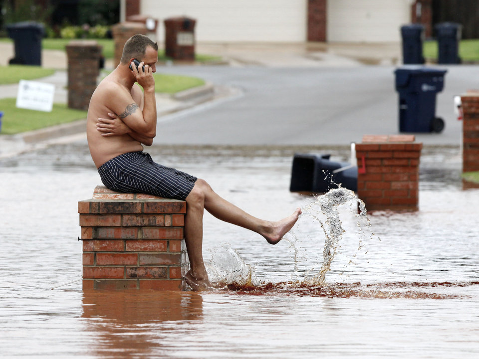 Daniel Parker splashes water while sitting on his mailbox in front of his house in the Palo Verde Addition in Edmond, OK, after flood waters inundated a number of homes in the area, Monday, June 14, 2010. By Paul Hellstern, The Oklahoman