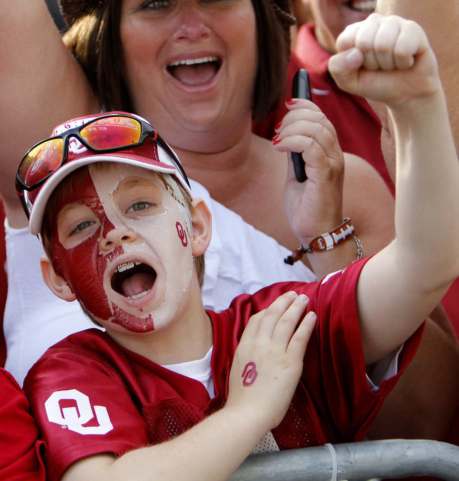 Photo - Oklahoma fan Jacob Green cheers on his team as the Sooners' team busses arrive for the Red River Rivalry college football game between the University of Oklahoma Sooners (OU) and the University of Texas Longhorns (UT) at the Cotton Bowl in Dallas, Saturday, Oct. 8, 2011. Photo by Chris Landsberger, The Oklahoman