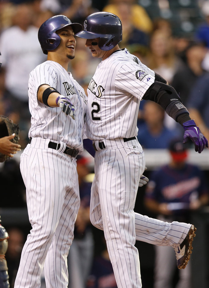 Photo - Colorado Rockies' Troy Tulowitzki (2) and Carlos Gonzalez (5) chest bump after scoring on Tulowitzki's two run home run hit off Minnesota Twins starting pitcher Kris Johnson during the third inning of a baseball game on Friday, July 11, 2014, in Denver. (AP Photo/Jack Dempsey)