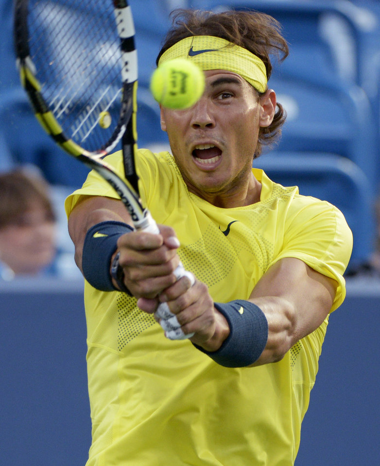 Photo - Rafael Nadal, from Spain, hits a return to Grigor Dimitrov, from Bulgaria, at the Western & Southern Open tennis tournament, Thursday, Aug. 15, 2013, in Mason, Ohio. (AP Photo/Michael E. Keating)