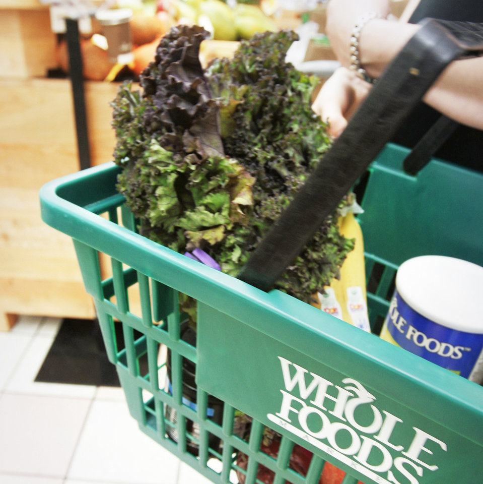 Photo - A woman carries a basket at a Whole Foods Market Inc., store on Tuesday in Little Rock, Ark.  AP Photo