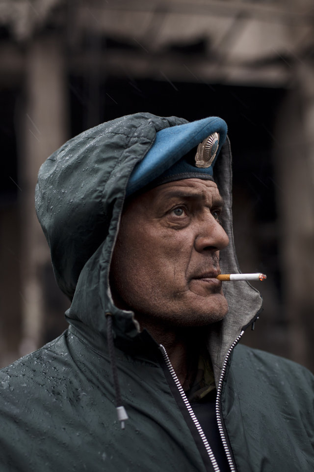 Photo - Dima, a member of a volunteer self defense group, smokes a cigarette during a rainfall in Kiev's Independence Square, Ukraine, Sunday, March 16, 2014. In a referendum watched closely around the world, residents in Ukraine's strategic Crimean Peninsula voted Sunday on whether to demand greater autonomy or split off and seek to join Russia. (AP Photo/David Azia)
