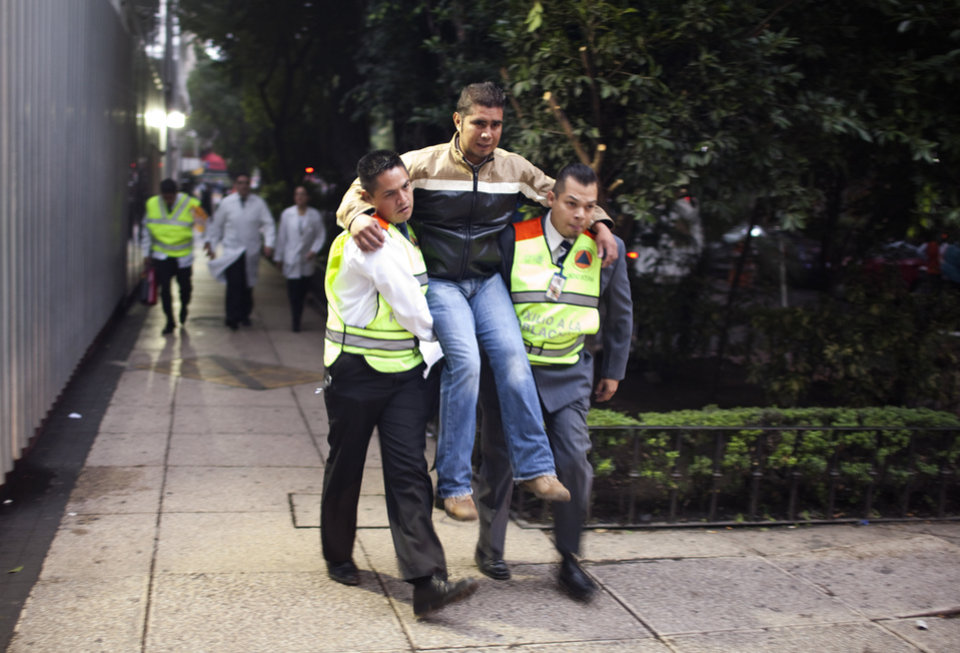 Photo - A man is carried on the sidewalk after he hurt his leg while fleeing a building during an earthquake in Mexico City, Wednesday, Aug. 21, 2013. The U.S. Geological Survey said the quake had a magtitude of 6.1 and was centered on the Pacific coast, near the resort of Acapulco. Buildings swayed in the capital and some people evacuated buildings as an earthquake alarm sounded. The alarm also went off for a second, smaller quake a few minutes later. (AP Photo/Ivan Pierre Aguirre)