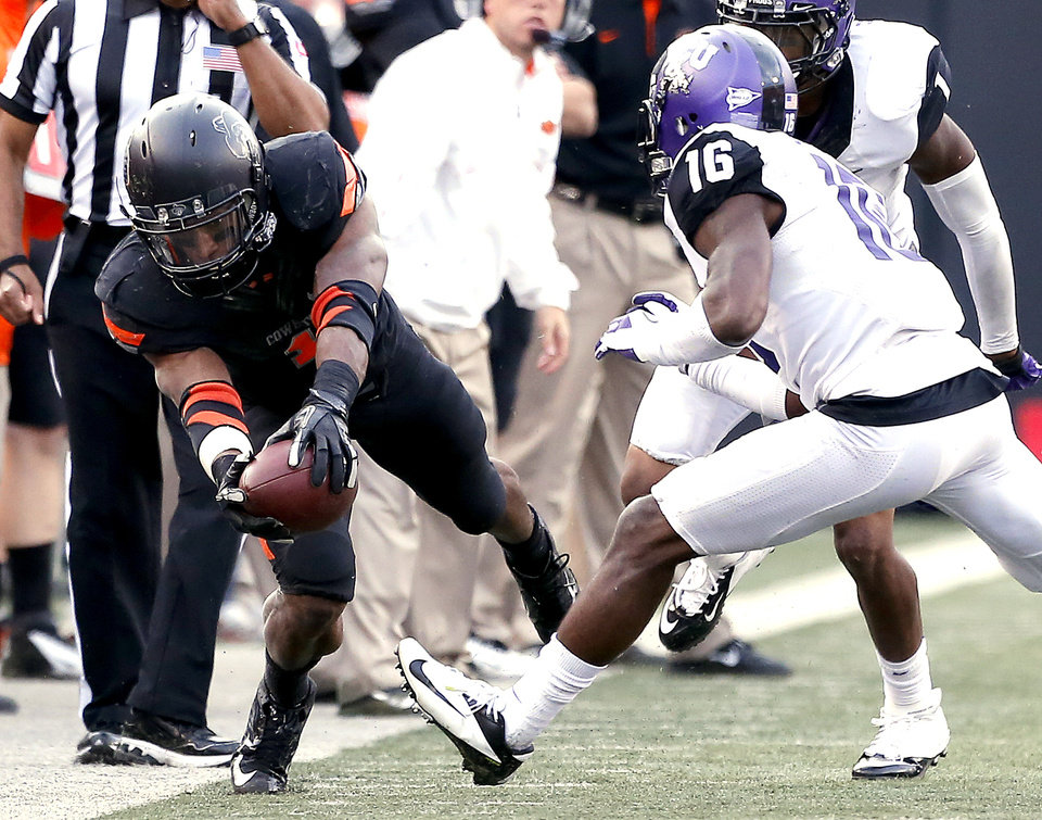 Photo - Oklahoma State's Joseph Randle (1) dives for a first down in front of TCU's Keivon Gamble (16) during a college football game between Oklahoma State University (OSU) and Texas Christian University (TCU) at Boone Pickens Stadium in Stillwater, Okla., Saturday, Oct. 27, 2012. Photo by Sarah Phipps, The Oklahoman