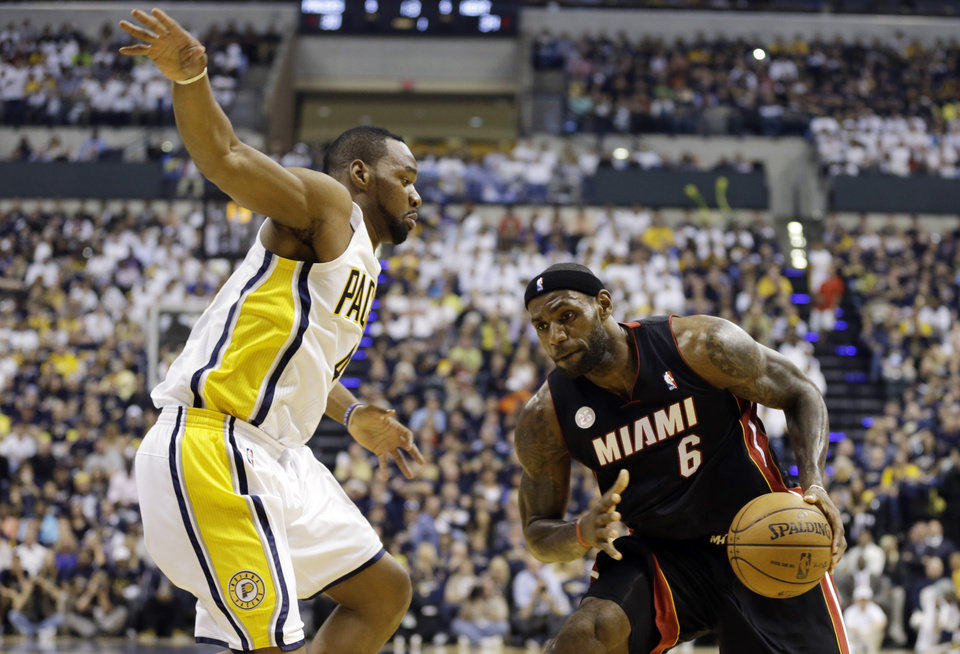 Photo - Miami Heat's LeBron James, right, is defended by Indiana Pacers' Sam Young during the first half of Game 3 of the NBA Eastern Conference basketball finals in Indianapolis, Sunday, May 26, 2013. (AP Photo/Nam H. Huh)