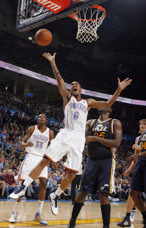 Photo - Oklahoma City's Eric Maynor shoots a lay up in front of Utah's Al Jefferson during the NBA basketball game between the Oklahoma City Thunder and Utah Jazz in the Oklahoma City Arena on Sunday, Oct. 31, 2010. Photo by Sarah Phipps, The Oklahoman