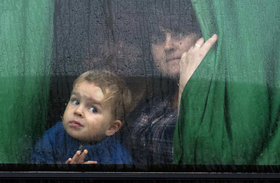 Photo - People look out a bus window as they depart to seek refugees to Russia in the city of Donetsk, eastern Ukraine Monday, July 14, 2014. Five busloads of Internally Displaced People from the towns of Slavyansk, Karlovka, Maryinka and Donetsk left here Monday morning for the Rostov region in Russia to ask for refugee status there. (AP Photo/Dmitry Lovetsky)