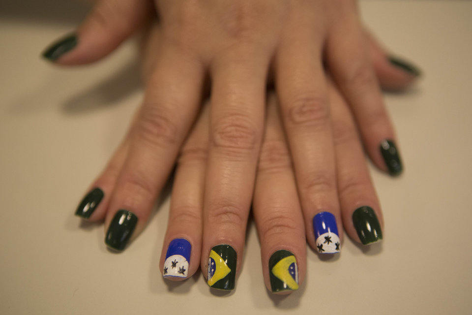 Photo - Fernanda Cavalcanti shows off her freshly painted nails at the Loar Beauty Salon in central, in Sao Paulo, Brazil, Tuesday, June 17, 2014. Forget the French manicure. It's Brazil during World Cup, and women here want to flaunt their love of the national team with wacky nail designs. It's not only the Brazilian flag on the hands of many Brazilian women. It's jerseys, soccer balls, soccer fields, the World Cup official mascot, and even Neymar's face, believe it or not. (AP Photo/Dario Lopez-Mills)