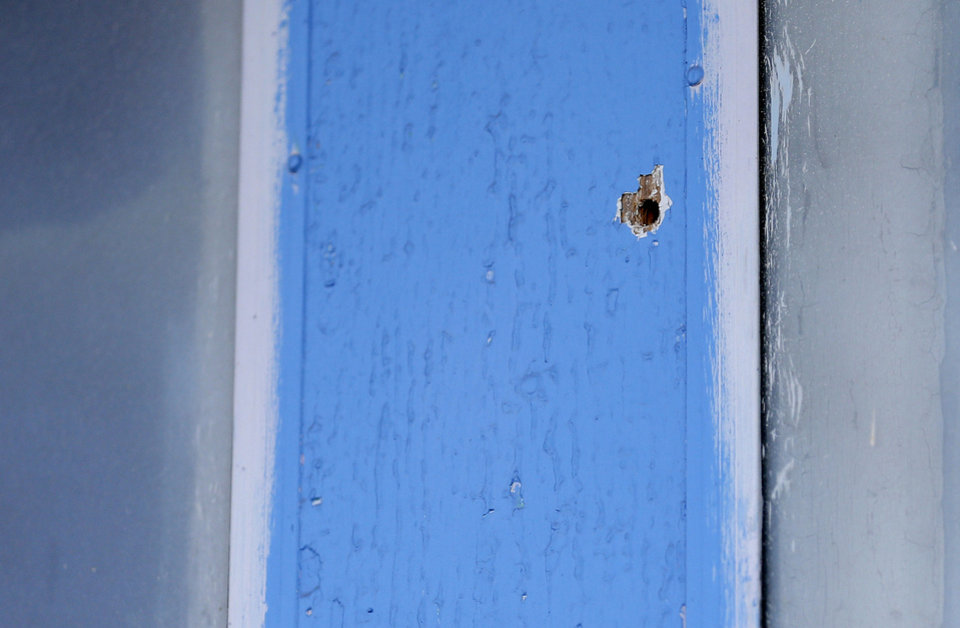 Photo - A bullet hole from a drive-by shooting is pictured Friday at the Taghavi home in southwest Oklahoma City. Photo by Sarah Phipps, The Oklahoman  SARAH PHIPPS