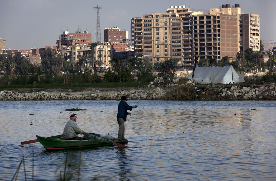 Photo - Two Egyptian fishermen work on their boat at the Nile river surrounding the Qursaya island, in Cairo, Egypt, Monday, Jan. 14, 2013. The Egyptian Armed Forces claims that it is the registered owner of the island's land, a claim disputed by the some 5,000 farmers and fishermen residents of the embattled island that have been resisting their eviction since 2007. (AP Photo/Nasser Nasser)