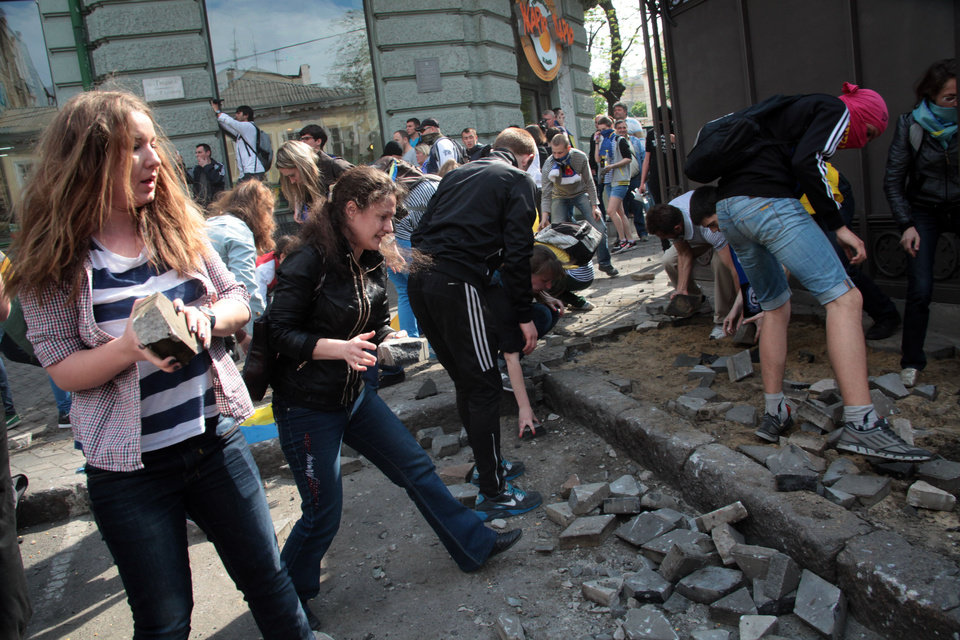 Photo - Ukrainian government supporters dig for stones during a clash with pro-Russians in the Black Sea port of Odessa, Ukraine, Friday, May 2, 2014. A clash broke out late Friday between pro-Russians and government supporters in Odessa, on the Black Sea coast some 550 kilometers (330 miles) from the turmoil in the east. Odessa had remained largely untroubled by unrest since the February toppling of pro-Russia President Viktor Yanukovych, which ignited tensions in the east. (AP Photo/Sergei Poliakov)
