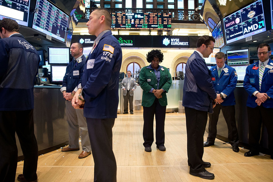 In this photo provided by the New York Stock Exchange Euronext, employees of the NYSE observe a moment of silence on the floor of the exchange in New York, Monday, April 22, 2013, a week after bombs exploded at the finish line of of the Boston Marathon. (AP Photo/NYSE Euronext, Ben Hider)
