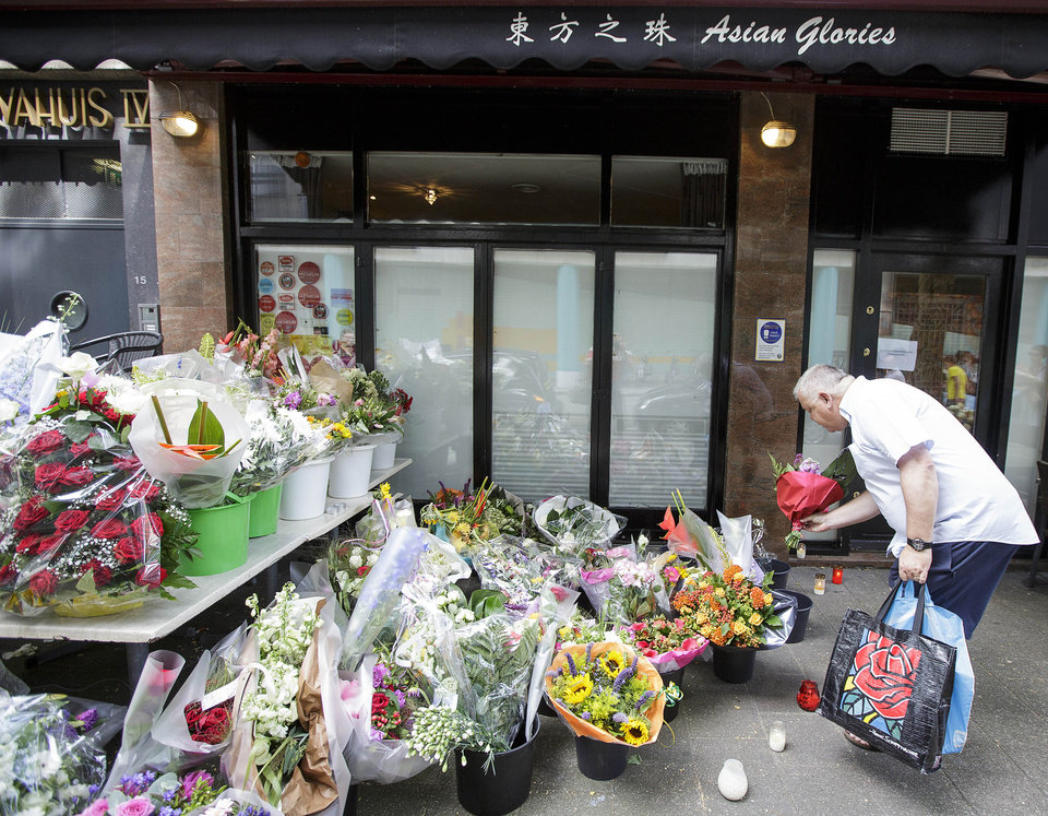 Photo - A man lays flowers in front of restaurant Asian Glories in Rotterdam, Saturday, July 19, 2014. Both owners, Jenny Loh and Popo Fan, were among those killed when a Malaysian jetliner was shot down over Ukraine Thursday. All passengers, 298 people from nearly a dozen nations, more than half being Dutch were killed. Malaysia Airlines said Saturday it has no immediate plans to fly the relatives of the 298 passengers and crew killed in the downing to visit the site in Ukraine because of security concerns. (AP Photo/Phil Nijhuis)