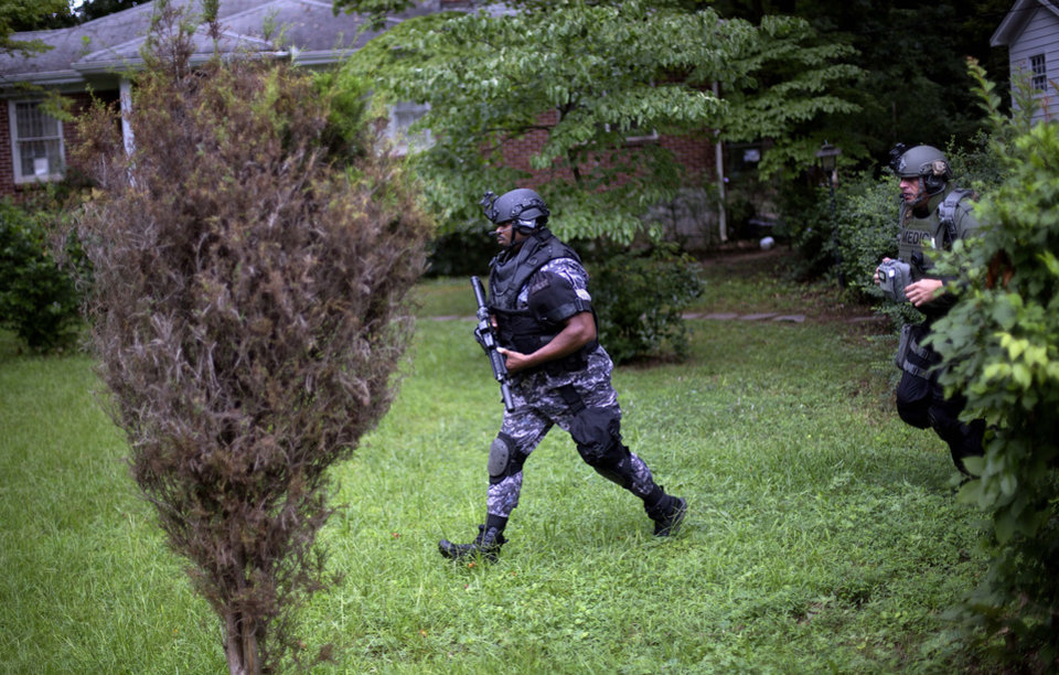 Photo - Dekalb County Police SWAT officers run though the front yard of a home toward Ronald E. McNair Discovery Learning Academy after reports of a gunman entered the school, Tuesday, Aug. 20, 2013, in Decatur, Ga.  Superintendent Michael Thurmond says all students at Ronald E. McNair Discovery Learning Academy in Decatur east of Atlanta are accounted for and safe Tuesday and that he is not aware of any injuries. (AP Photo/David Goldman)