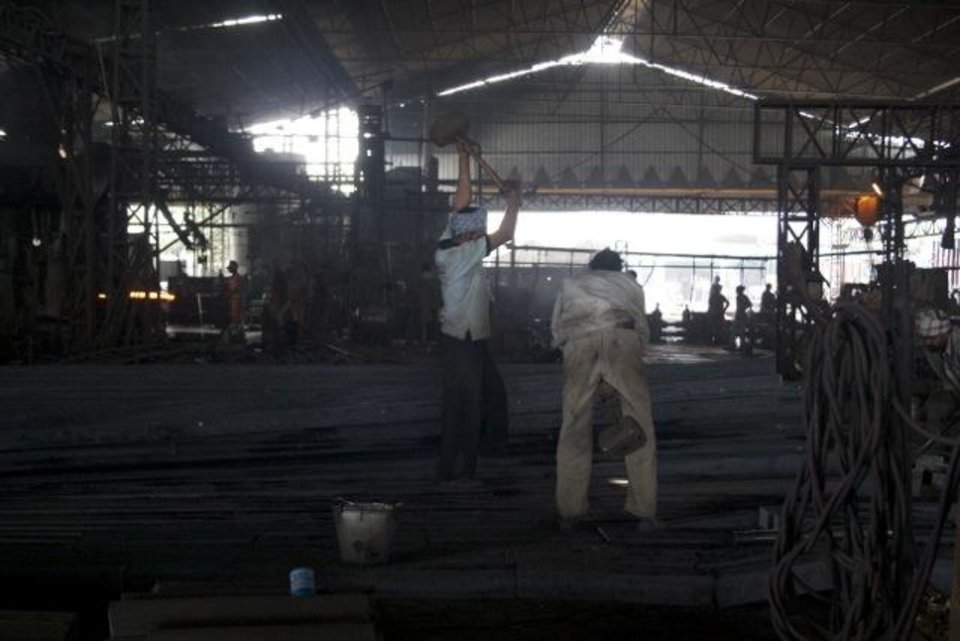 Photo -  These two men worked in tandem, dropping enormous sledge hammers to cut the steel pieces into smaller sections.
