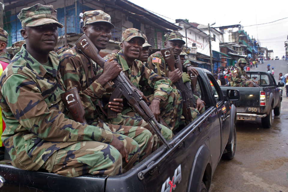Photo - Liberian security forces patrol the entrance to West Point that has been hardest hit by the Ebola virus spreading in Monrovia, Liberia, Monday, Aug. 25, 2014.  A Liberian doctor who was among three Africans to receive an experimental Ebola drug has died, the country's information minister said Monday.(AP Photo/Abbas Dulleh)