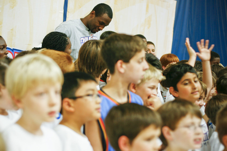 Serge Ibaka stands to pose with kids at the Thunder Youth Basketball Camp at the Santa Fe Family Life Center on Tuesday, June 14, 2011. Photo by Zach Gray, The Oklahoman