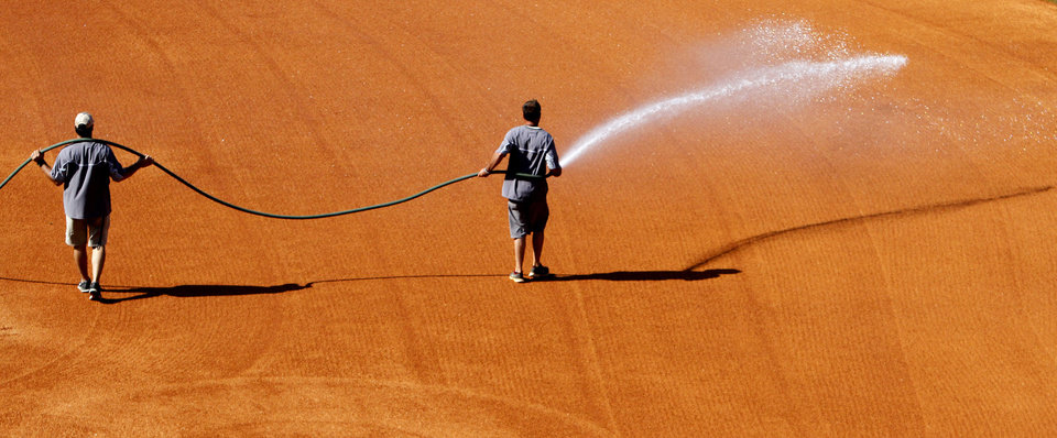 Photo - In this May 22, 2014 photo, grounds crew members spray the infield at the Southeastern Conference NCAA college baseball tournament on Thursday, May 22, 2014, in Hoover, Ala. (AP Photo/Butch Dill)