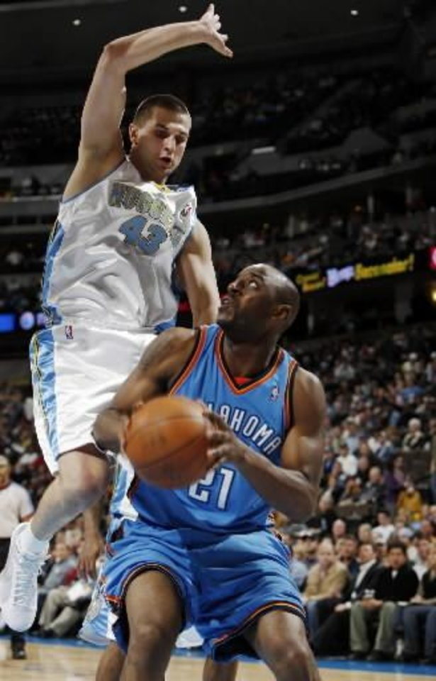 Oklahoma City Thunder forward Damien Wilkins, front, is fouled as he goes up for a shot by Denver Nuggets forward Linas Kleiza, of Lithuania, in the fourth quarter of the Nuggets\' 112-99 victory in an NBA basketball game in Denver on Wednesday, March 11, 2009. (AP Photo/David Zalubowski)