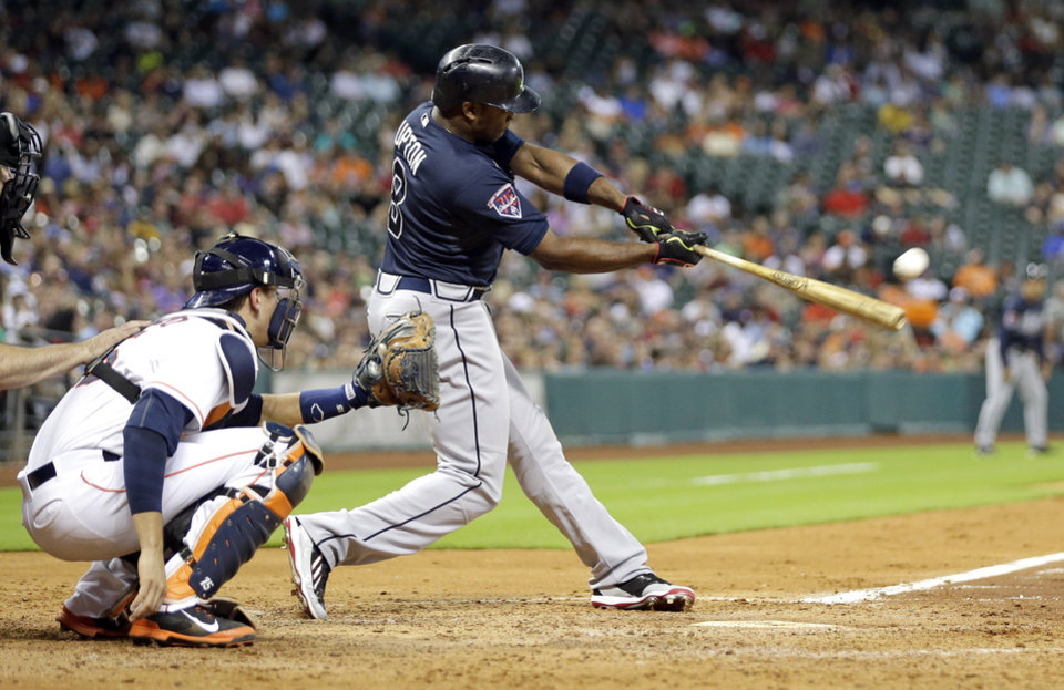 Photo - Atlanta Braves' Justin Upton (8) hits a home run in front of Houston Astros catcher Jason Castro during the fourth inning of a baseball game Tuesday, June 24, 2014, in Houston. (AP Photo/David J. Phillip)