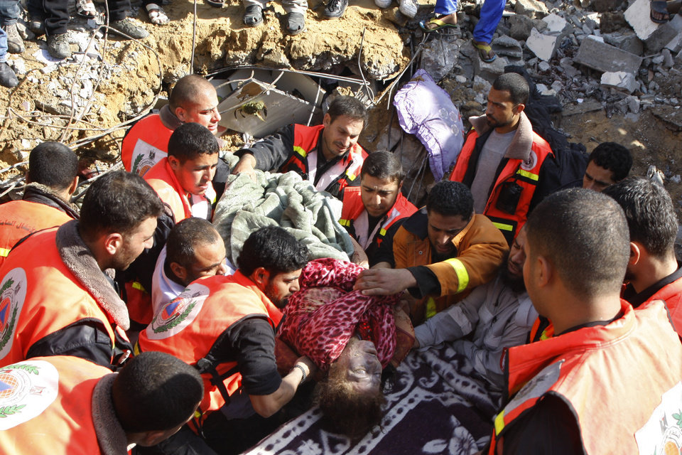 Photo -   The dead body of a Palestinian woman from the Abdel Aal family is pulled out from the rubble after the family house collapsed during an Israeli forces strike in the Tufah neighbourhood, Gaza City, Sunday, Nov. 18, 2012. The Israeli military widened its range of targets in the Gaza Strip on Sunday to include the media operations of the Palestinian territory's Hamas rulers, sending its aircraft to attack two buildings used by both Hamas and foreign media outlets. (AP Photo/Majed Hamdan)