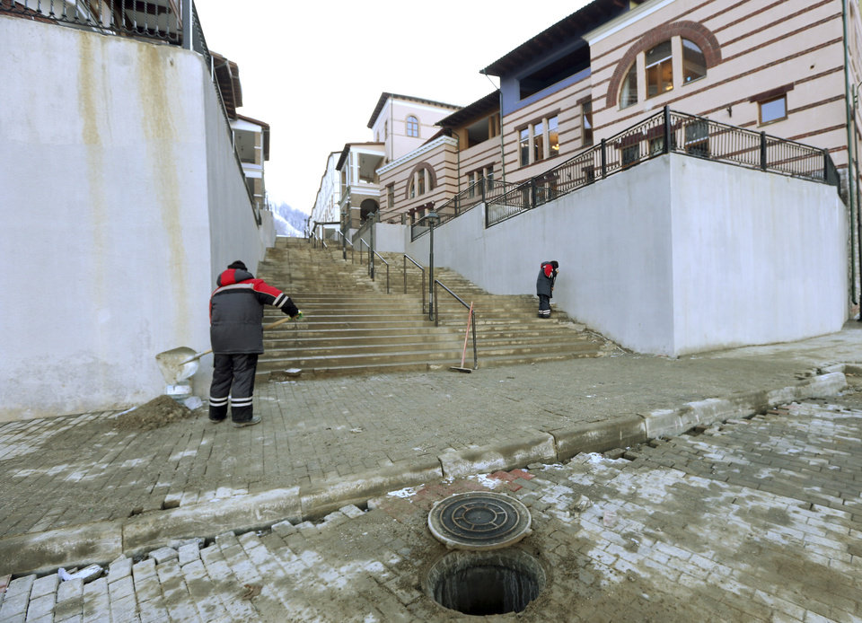 Photo - Workers clean the area outside the Panorama hotel in Krasnaya Polyana, Russia Sunday, Feb. 2, 2014. The IOC is urging Russian Olympic organizers to move quickly to resolve the issue of accommodations that are not ready for accredited media personnel in the mountains outside Sochi. According to the 2014 Sochi Winter Olympic organizing committee, only six of the nine media hotels in the mountain area are fully operational. (AP Photo/Luca Bruno)