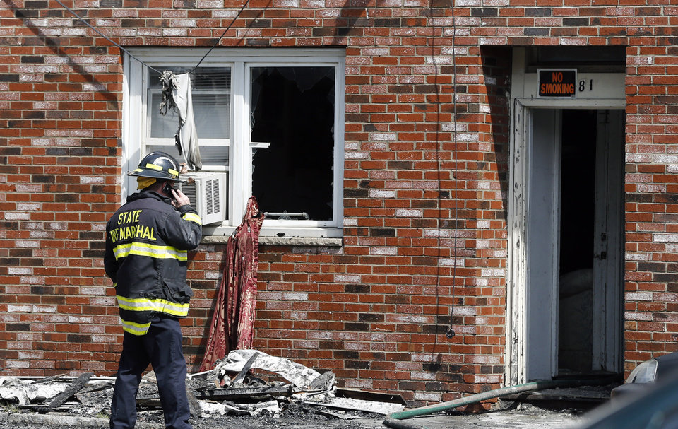 Photo - A state fire marshall talks on a cellphone at the scene of a burned three-story apartment and business building in Lowell, Mass., Thursday, July 10, 2014, where officials said seven people died in a fast-moving pre-dawn fire.  All seven victims were found in third-floor units of the three-story building that had businesses on the ground floor and apartments on the upper floors, fire officials said.  (AP Photo/Elise Amendola)