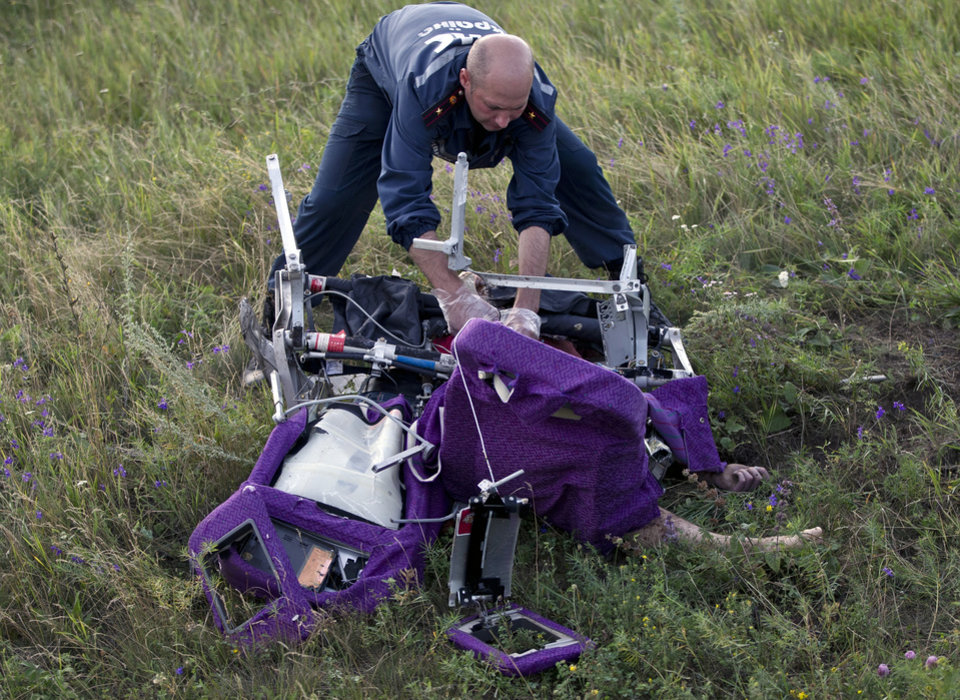 Photo - An emergency worker cuts through aircraft seat belts to free the body of a victim at the crash site of Malaysia Airlines Flight 17 near the village of Hrabove, eastern Ukraine, Saturday, July 19, 2014. International monitors moved gingerly Saturday through fields reeking of the decomposing corpses that fell from a Malaysian airliner shot down over rebel-held eastern Ukraine, trying to secure the sprawling site in hopes that a credible investigation can be conducted. (AP Photo/Vadim Ghirda)