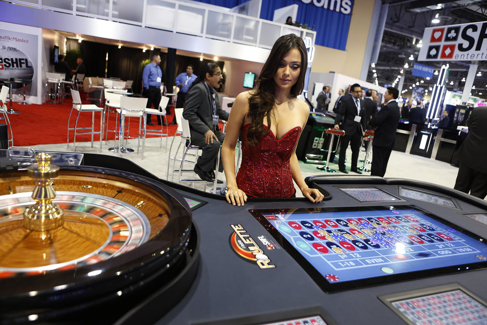 Photo -   Yohanna Thomas of Las Vegas, demonstrates a video roulette shell during the Global Gaming Expo on Wednesday, Oct. 3, 2012, in Las Vegas. While casino executives agree that internet gambling is inevitable, they question whether state or federal authorities should regulate it.(AP Photo/Isaac Brekken)
