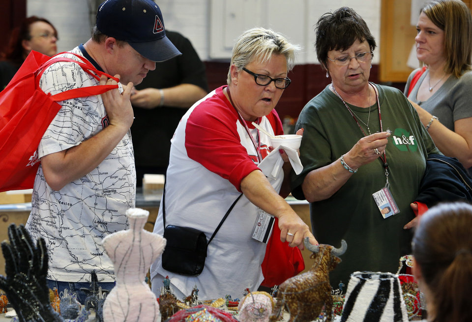 Housekeeping workers Dusty Baker, Debbie Sugg and Pam Ross look at art during an ice cream social and craft fair sponsored by Hourly Employees at the University of Oklahoma (OU) for Staff Appreciation Week on Thursday, April 24, 2014, in Norman, Okla. Photo by Steve Sisney, The Oklahoman
