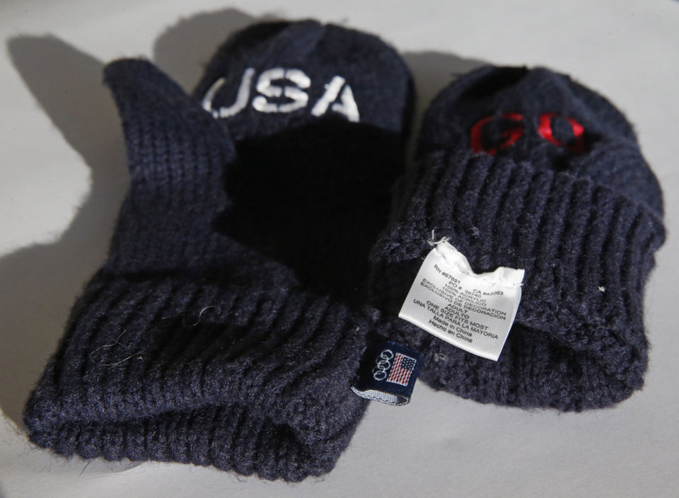 "In this Dec. 16, 2013 photo, embroidered mittens that the U.S. Olympic Committee are selling as part of a fundraiser, are shown, in Denver. The U.S. Olympic Committee is charging $14 a pair for the blue gloves that have the word ""Go"" embroidered in red on one mitten and ""USA"" on the other. The pair is also labeled with a tag on the inside which says the gloves are ""Made in China."" The foreign-made mittens are available at the USOC's official online shop of the U.S. Olympic Team. (AP Photo/Brennan Linsley)"