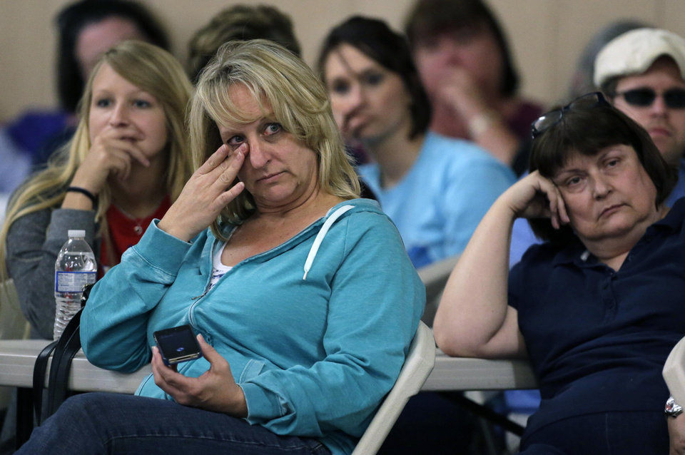 Photo - West, Texas residents listen during a town hall meeting Saturday, April 20, 2013, three days after an explosion at a fertilizer plant in West, Texas. The massive explosion at the West Fertilizer Co. Wednesday night killed 14 people and injured more than 160. (AP Photo/Charlie Riedel)
