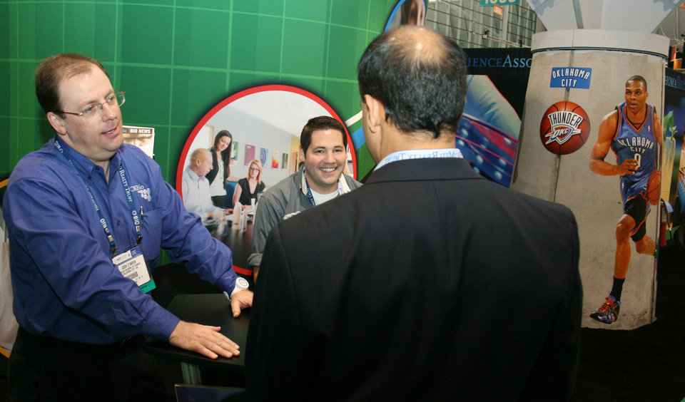 Photo - Josh O?Brien, left, from i2E and the Greater Oklahoma City Chamber, talking to a visitor Wednesday at the BIO International convention in Boston. PHOTO BY JIM STAFFORD     unknown