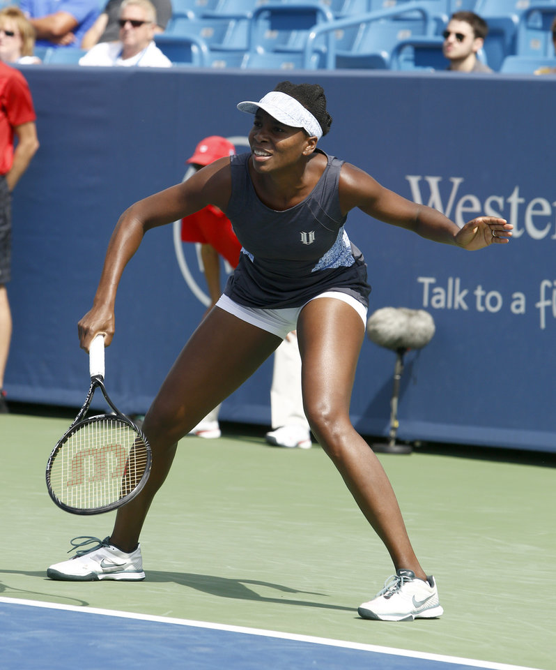 Photo - Venus Williams waits for a shot from Lucie Safarova, from Czech Republic, during a first round match at the Western & Southern Open tennis tournament, Tuesday, Aug. 12, 2014, in Mason, Ohio. (AP Photo/David Kohl)