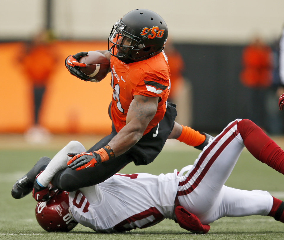 Photo - Oklahoma's Quentin Hayes (10) stops Oklahoma State's Jeremy Smith (31) in the third quarter during the Bedlam college football game between the Oklahoma State University Cowboys (OSU) and the University of Oklahoma Sooners (OU) at Boone Pickens Stadium in Stillwater, Okla., Saturday, Dec. 7, 2013. OU won, 33-24. Photo by Nate Billings, The Oklahoman