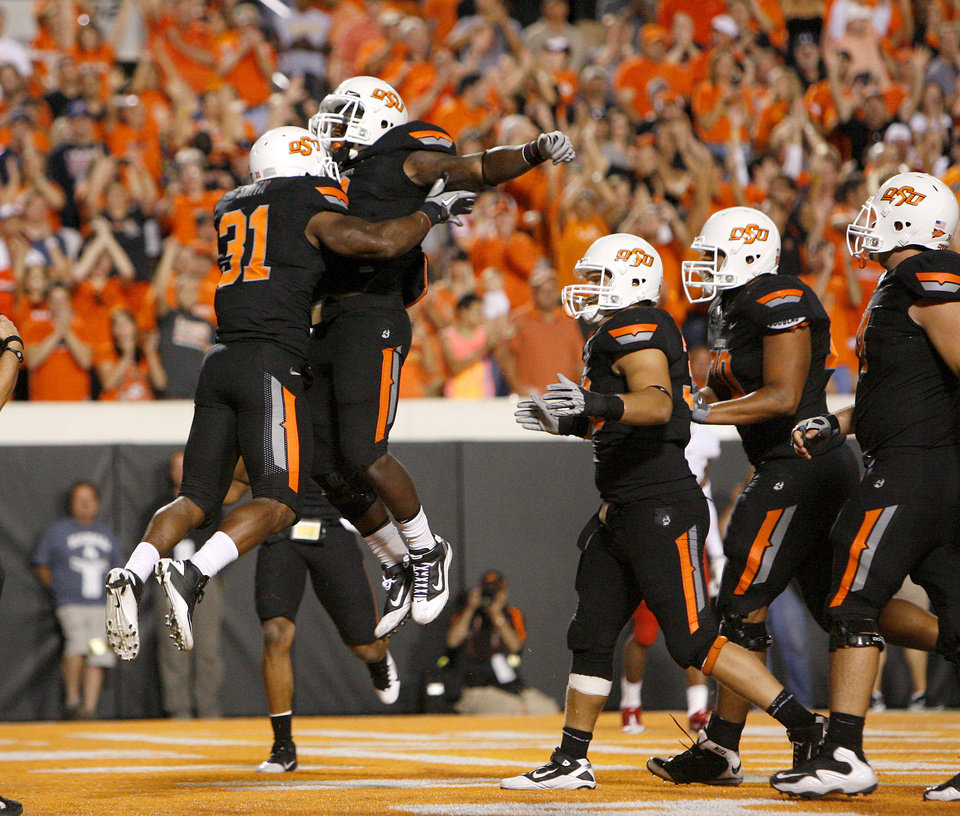 Photo - Oklahoma State's Jeremy Smith celebrates with Kye Staley after Smith scored a touchdown Thursday. BY BRYAN TERRY, The Oklahoman
