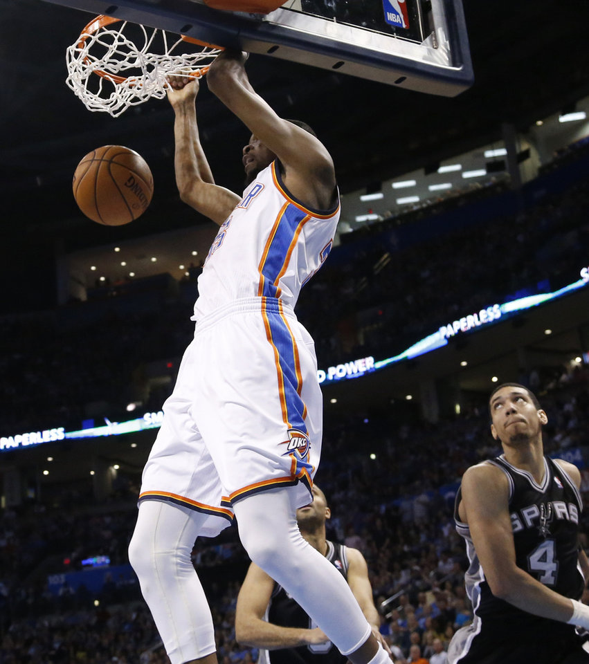 Photo - Oklahoma City Thunder forward Kevin Durant (35) dunks in front of San Antonio Spurs guard Tony Parker and guard Danny Green (4) in the second quarter of an NBA basketball game in Oklahoma City, Thursday, April 3, 2014. (AP Photo/Sue Ogrocki)