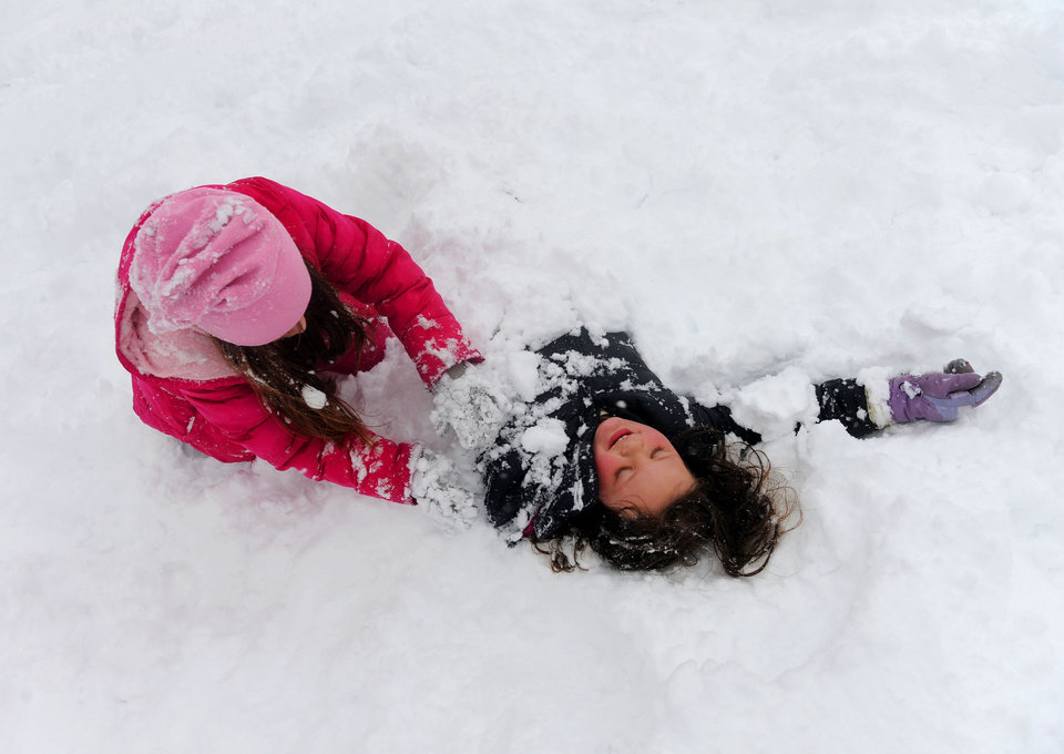 Photo - Ashton Lam, right, 8, is buried in the snow by friend Ava Miller, 10, as they enjoy the winter weather in Staunton, Va, on Wednesday, March 6, 2012.  The March snowstorm is primarily hitting a region stretching from central Virginia to the northern and western portions of the state, where snow is piling up quickly.  (AP Photo/The News Leader, Mike Tripp) NO SALES