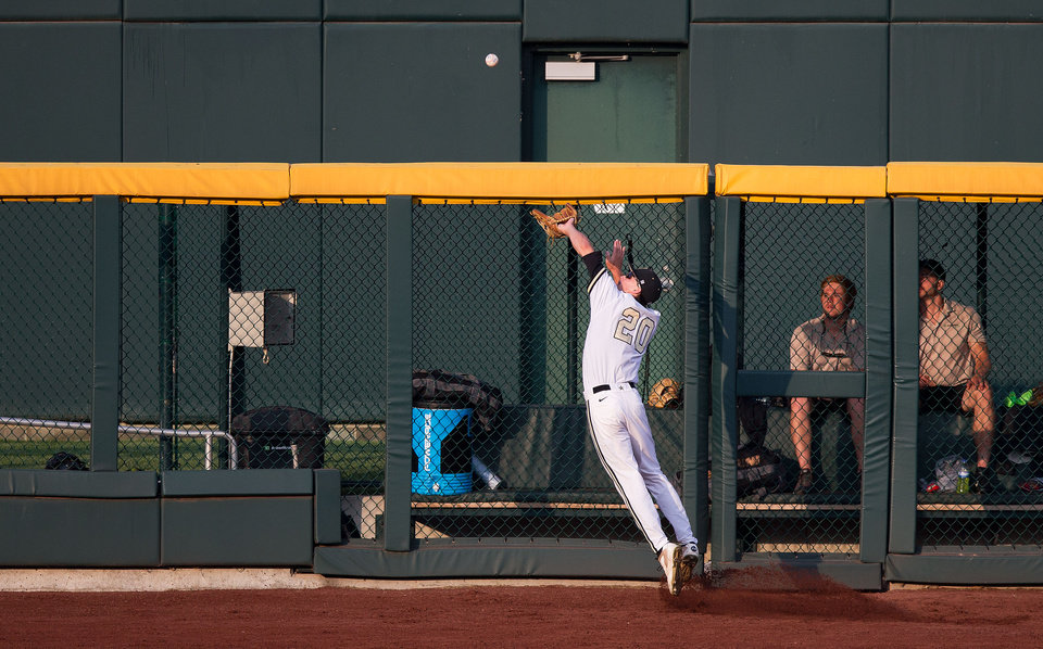 Photo - Vanderbilt left fielder Bryan Reynolds (20 ) catches a fly ball during the second inning against Louisville at the College World Series on Saturday, June 14, 2014, in Omaha, Neb. (AP Photo/Omaha World-Herald, Sarah Hoffman) MAGAZINES OUT; ALL LOCAL TELEVISION OUT
