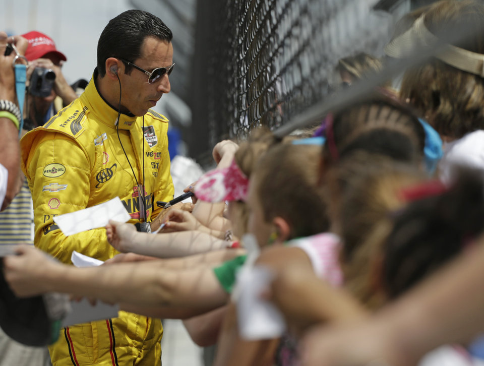Photo - Helio Castroneves, of Brazil, signs autographs for fans during practice for Indianapolis 500 IndyCar auto race at the Indianapolis Motor Speedway in Indianapolis, Monday, May 12, 2014. (AP Photo/Darron Cummings)