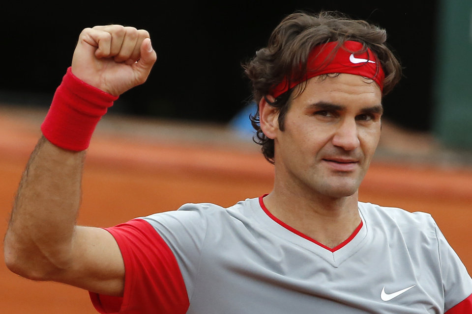 Photo - Switzerland's Roger Federer celebrates winning the third round match of the French Open tennis tournament against Russia's Dmitry Tursunov at the Roland Garros stadium, in Paris, France, Friday, May 30, 2014.  Federer won in four sets 7-5, 6-7, 6-2, 6-4. (AP Photo/Michel Euler)