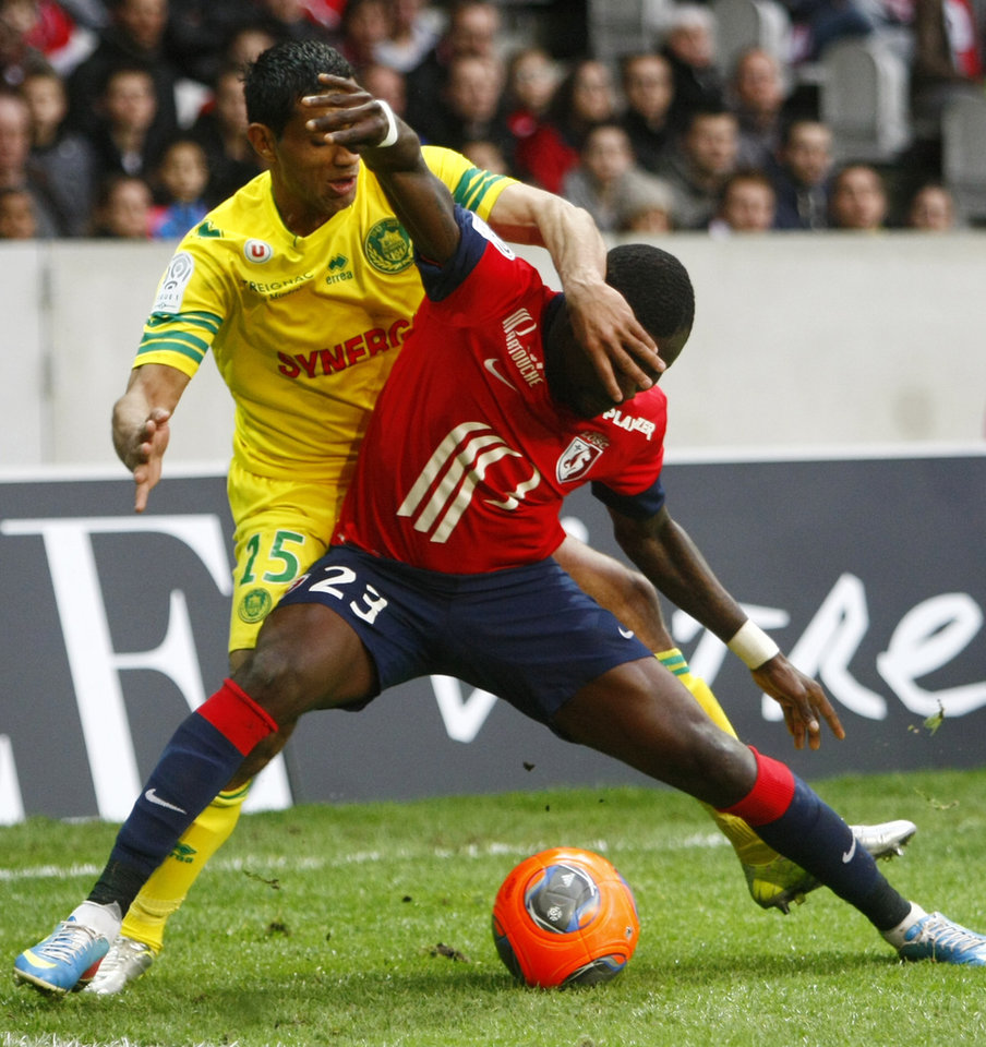 Photo - Nantes' Banel Nicolita and Lille's Adama Soumaoro, front, challenge the ball during their French League one soccer match at the Lille Metropole stadium, in Villeneuve d'Ascq, northern France, Saturday, March 15, 2014. (AP Photo/Michel Spingler)