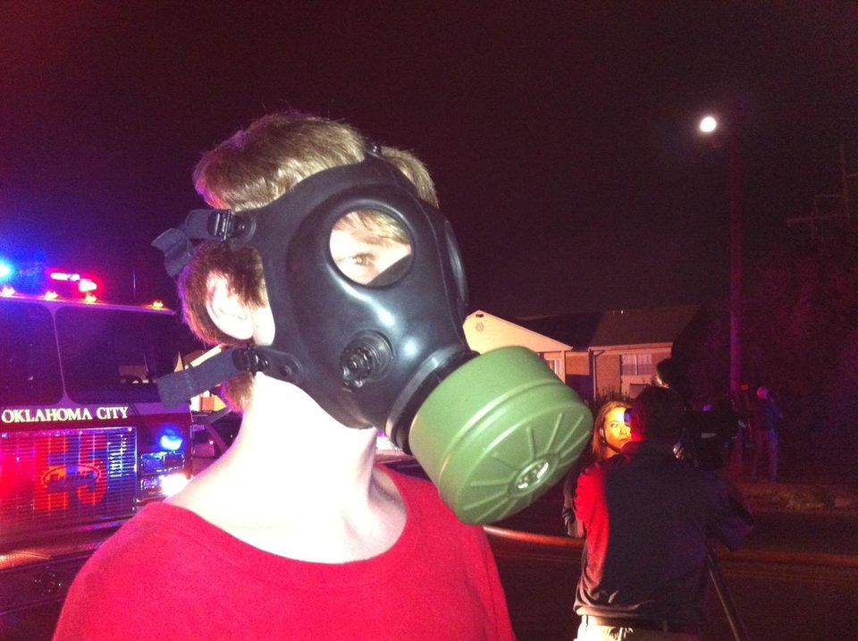 Zachary Scott Harnden, 17, wears a gas mask at the Ambassador House Apartment fire. He called 911 Thursday. He said he collects military surplus supplies and used it during fire. His apartment was not damaged. Photo by Robert Medley