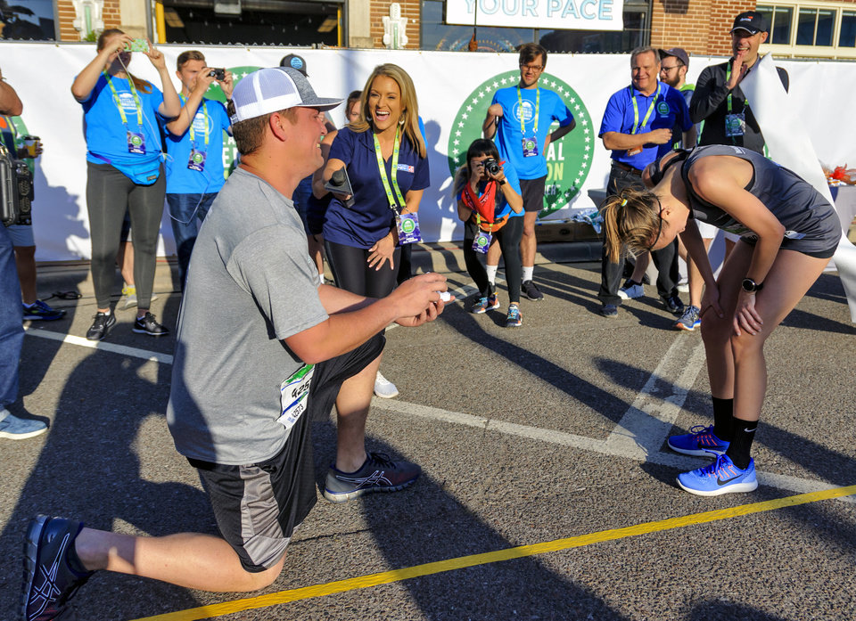 Photo - Tara Lewis reacts as Tyler Grimes proposes to her after she crossed the finish line to complete the half marathon during the Oklahoma City Marathon in Oklahoma City, Okla. on Sunday, April 29, 2018.  . Photo by Chris Landsberger, The Oklahoman