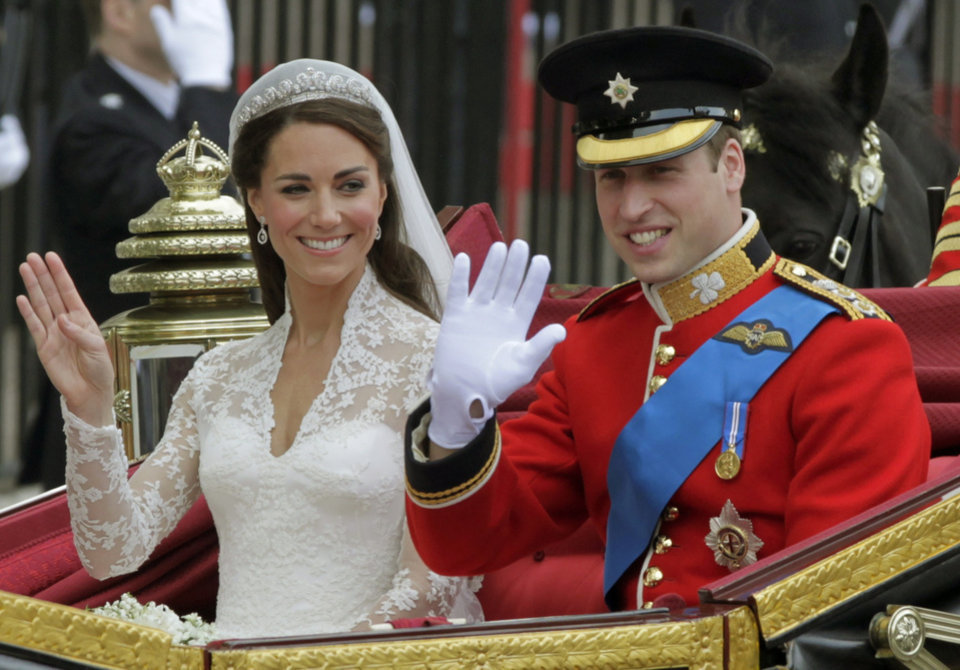 Photo - Britain's Prince William and his wife Kate, Duchess of Cambridge, left, wave as they leave Westminster Abbey at the Royal Wedding in London Friday, April, 29, 2011. (AP Photo/Alastair Grant)  ORG XMIT: RWFO146