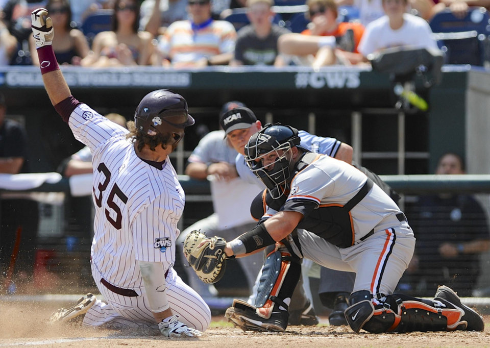 Photo - Mississippi State's Wes Rea (35) is tagged out at home plate by Oregon State catcher Jake Rodriguez after Trey Porter fouled out on a double play in the fourth inning of an NCAA College World Series baseball game in Omaha, Neb., Friday, June 21, 2013. (AP Photo/Eric Francis)